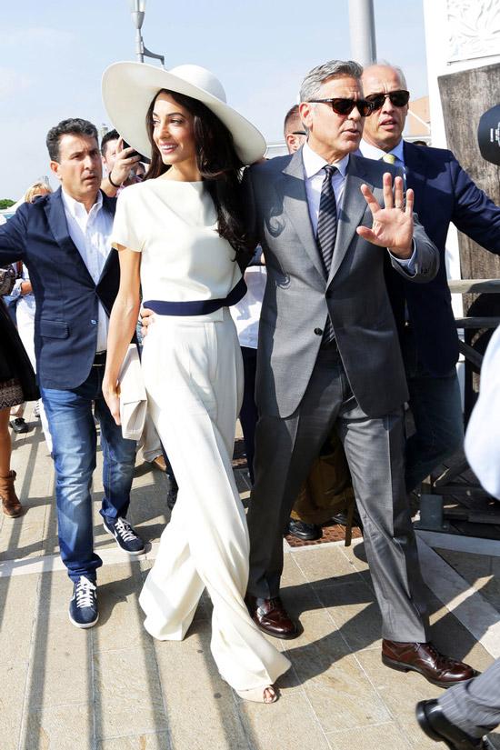 Амаль Клуни в белых широких брюках, белая футболка и шляпа, Джордж Клуни в сером костюме
