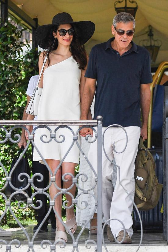 Амаль Клуни в простом белом платье, Джордж Клуни в черной футболке и белых брюках