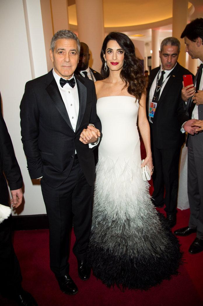 Амаль Клуни в вечернем платье с перьями, Джордж Клуни в черном смокинге