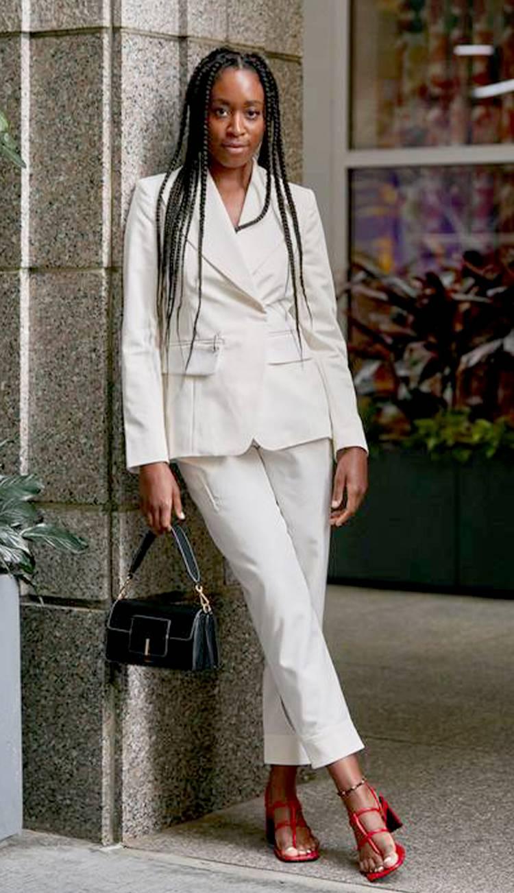 Девушка в белом брючном костюме, красные босоножки и черная сумочка
