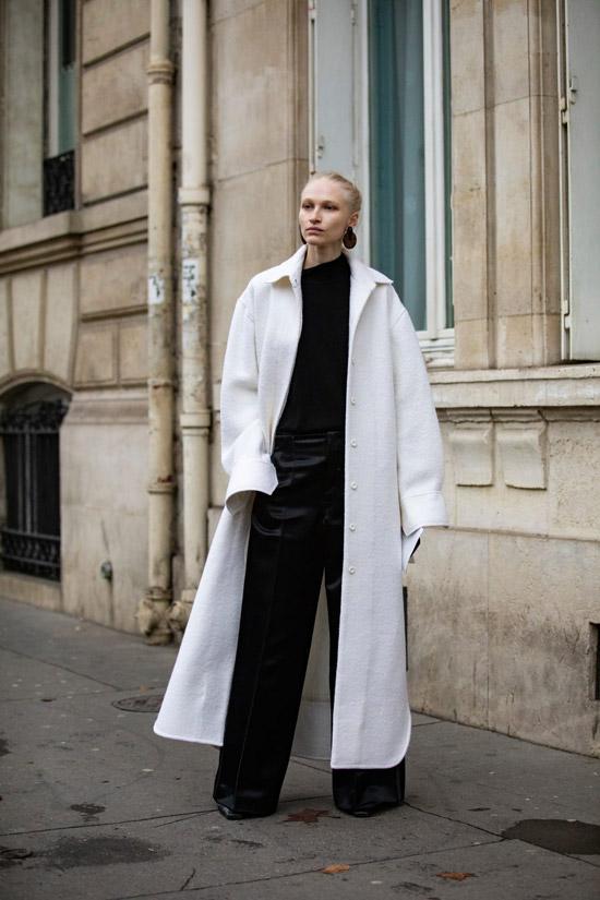 Девушка в белом длинном пальто, черные широкие брюки и водолазка