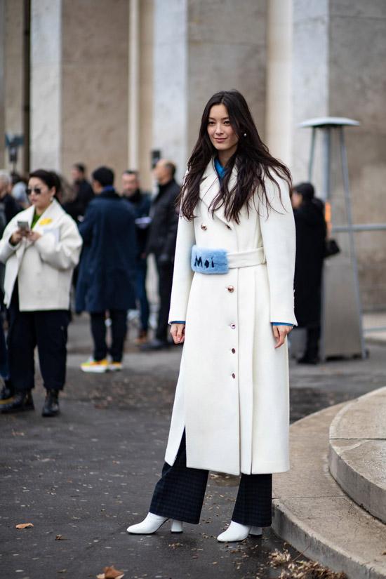Девушка в белом пальто с поясом, серые брюки и белые ботильоны