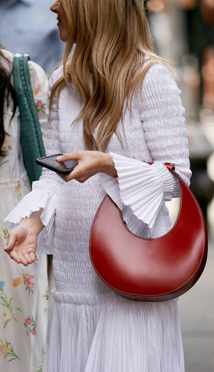 Девушка в белом платье с воланами и красная круглая сумочка