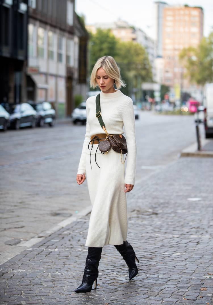 Девушка в белом трикотажном костюме, черные сапоги на шпильке и сумочка через плечо