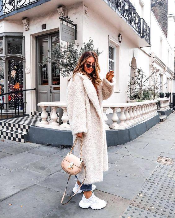 Девушка в белой длинной шубе, укороченные джинсы и белые кроссовки