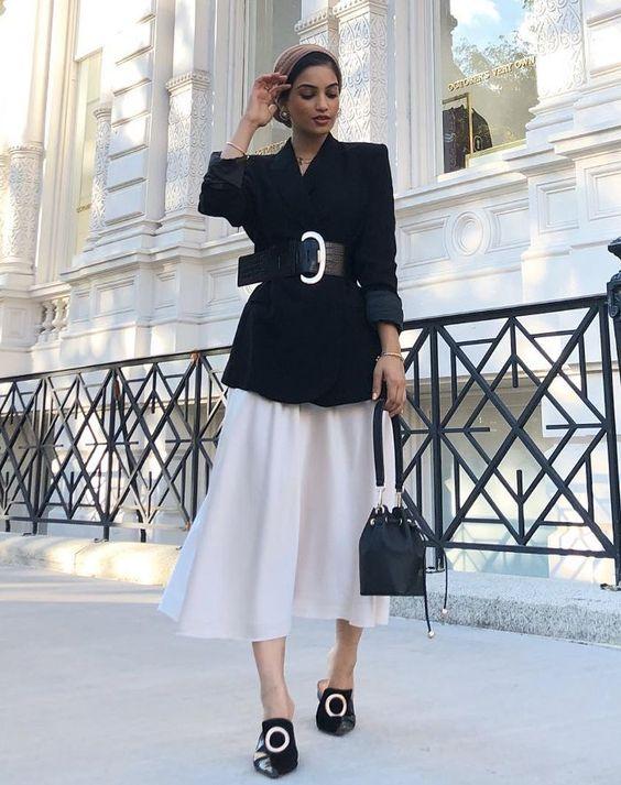 Девушка в белой юбке миди, черный блейзер с толстым ремнем и лоферы