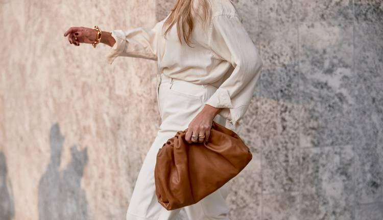 Девушка в белых брюках, блузка и кориневый мягкий клатч