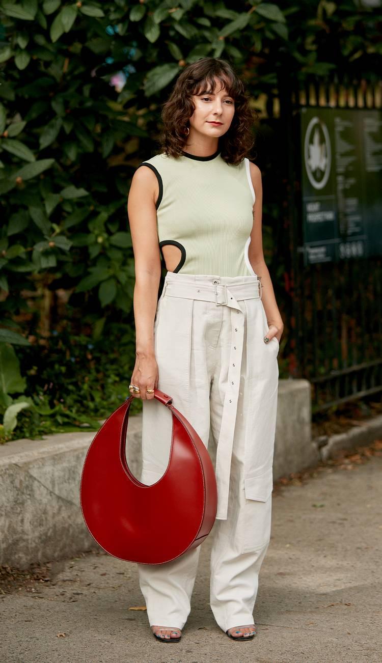 Девушка в белых брюках с поясом, майка и красная круглая сумка