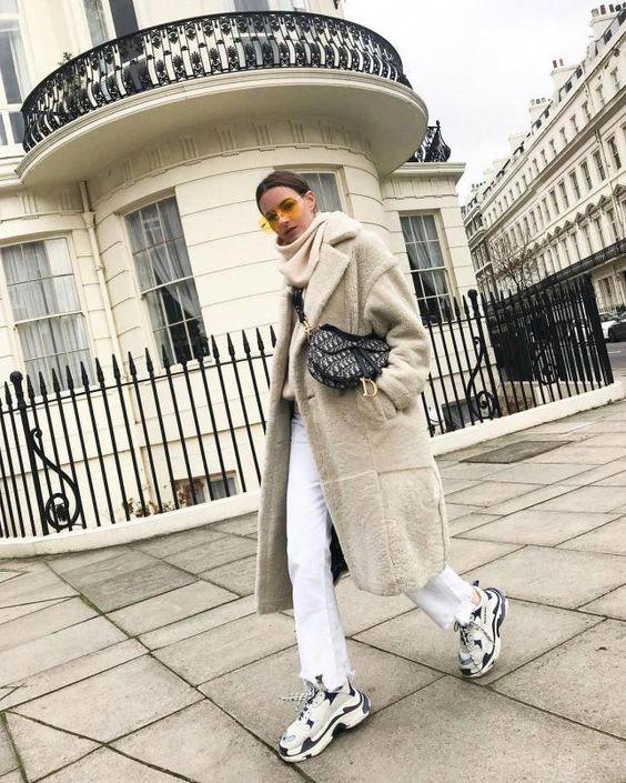 Девушка в белых джинсах, кроссовки и серое пальто
