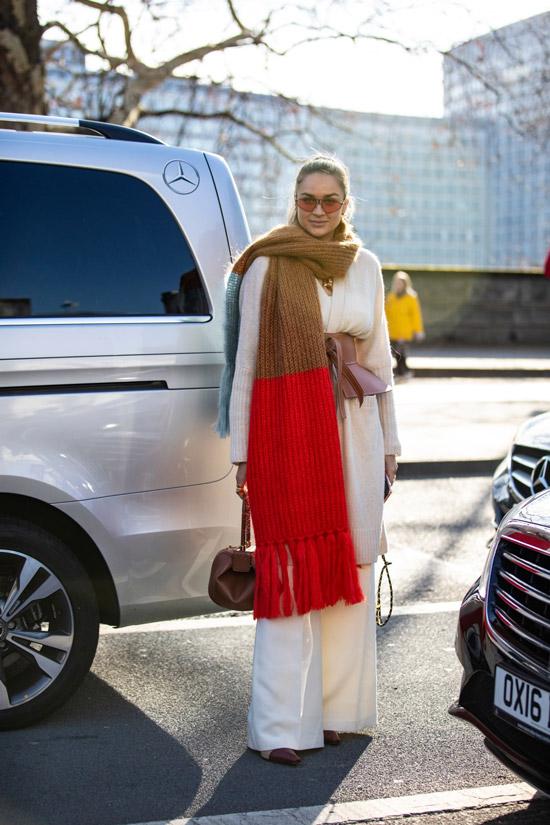 Девушка в белых широких брюках, джемпер и большой вязанный свитер