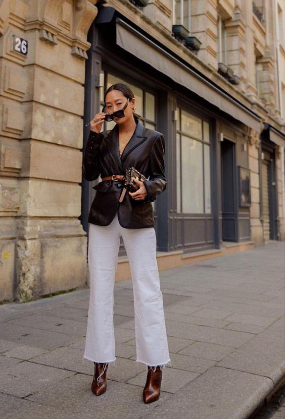 Девушка в белых укороченных джинсах, кожаный блейзер с ремнем и коричневые ботильоны