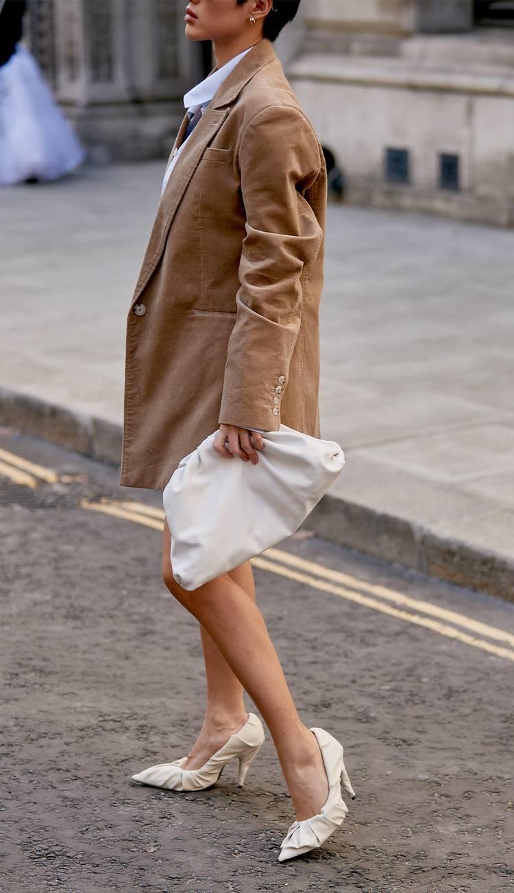 Девушка в бежевом блейзере оверсайз, белые туфли и мягкий клатч