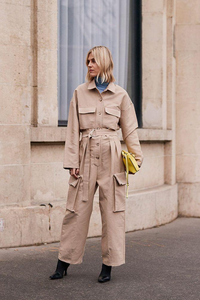 Девушка в бежевом комбинезоне с карманами, желтая сумочка и черные ботильоны