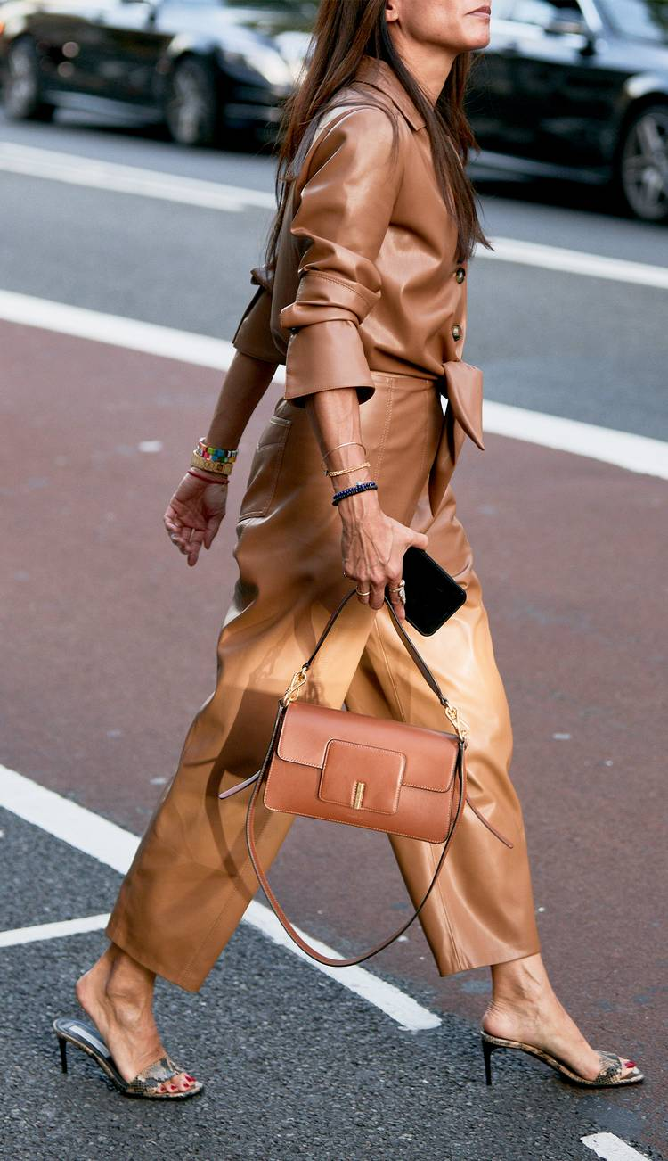 Девушка в бежевом кожаном комбинезоне, босоножки на каблуке и сумочка