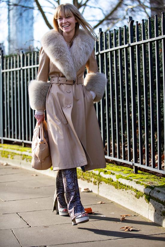 Девушка в бежевом плаще с меховыми манжетами и воротником, брюки и сумка
