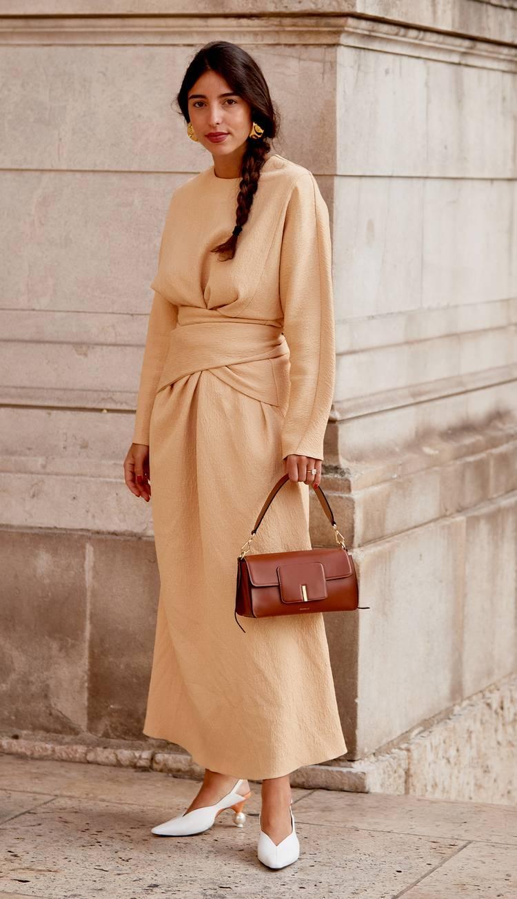 Девушка в бежевом платье с длинными рукавами и коричневая сумка