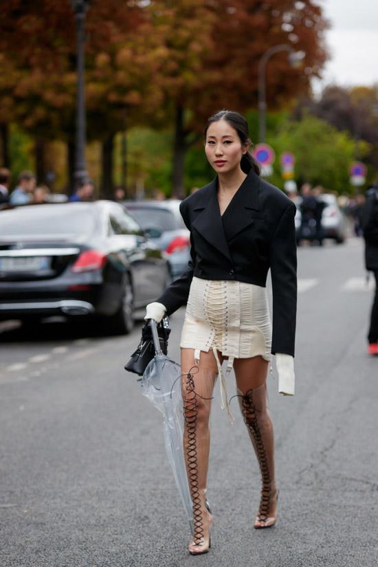 Девушка в бежевой мини юбке, черный жакет с удлиненными рукавами и прозрачные ботфорты на шнуровке