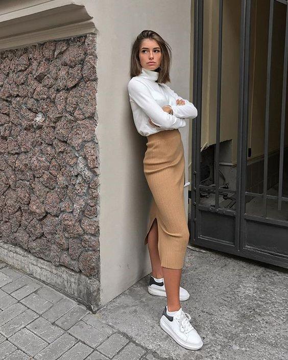 Девушка в бежевой юбке карандаш, светлая водолазка и белые кроссовки