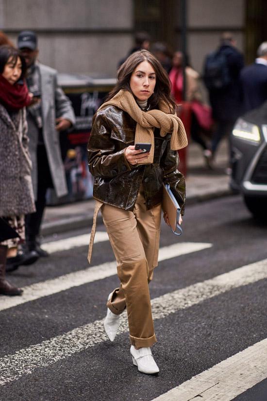 Девушка в бежевых брюках, кожаная куртка и вязанный свитер на шее