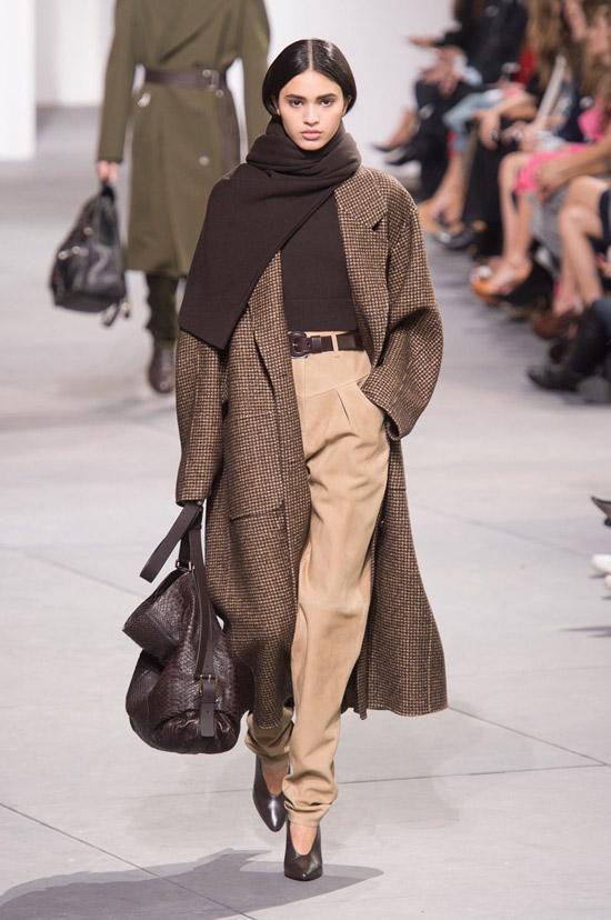 Девушка в бежевых брюках с ремнем, черная водолазка, коричневое пальто в клетку и большая сумка