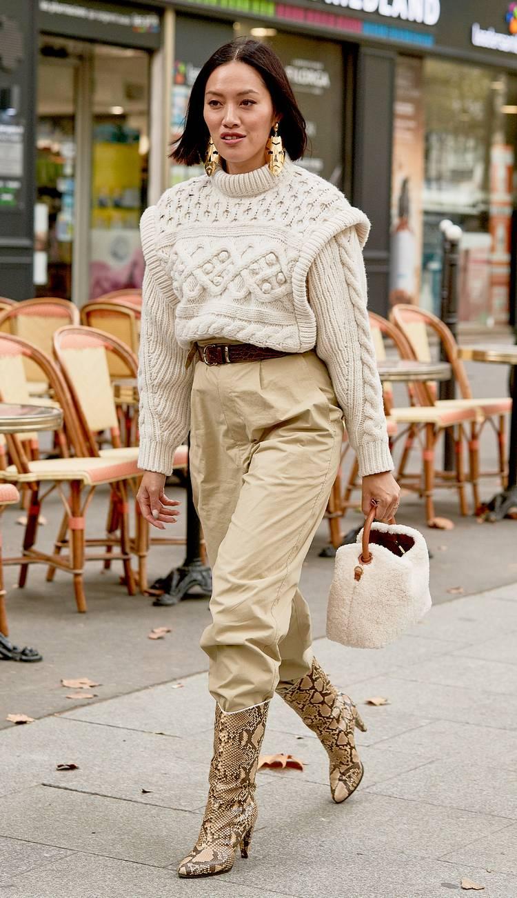 Девушка в бежевых брюках, толстый свитер и сапоги из змеиной кожи