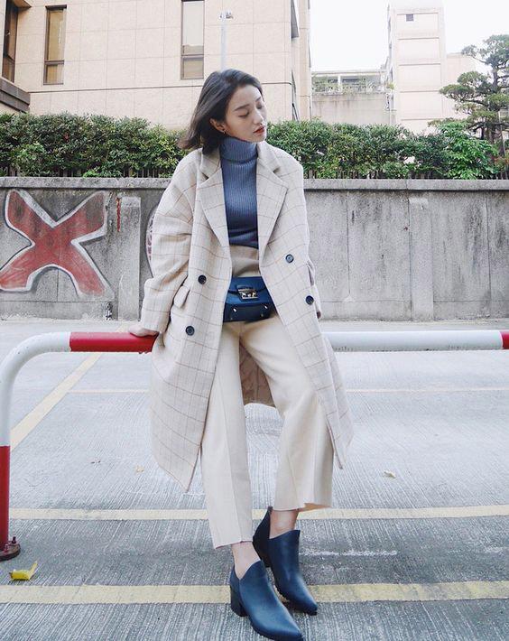 Девушка в брюках молочного цвета, пальто в клетку и черные ботильоны