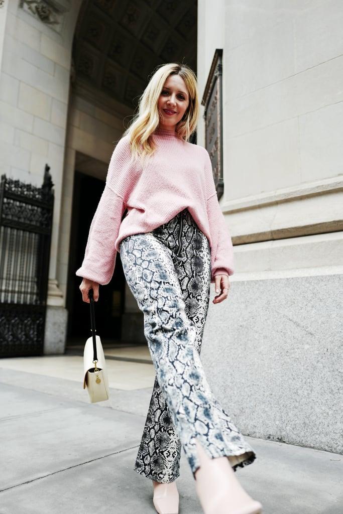 Девушка в брюках со змеинным прином, розовый свитер и ботильоны