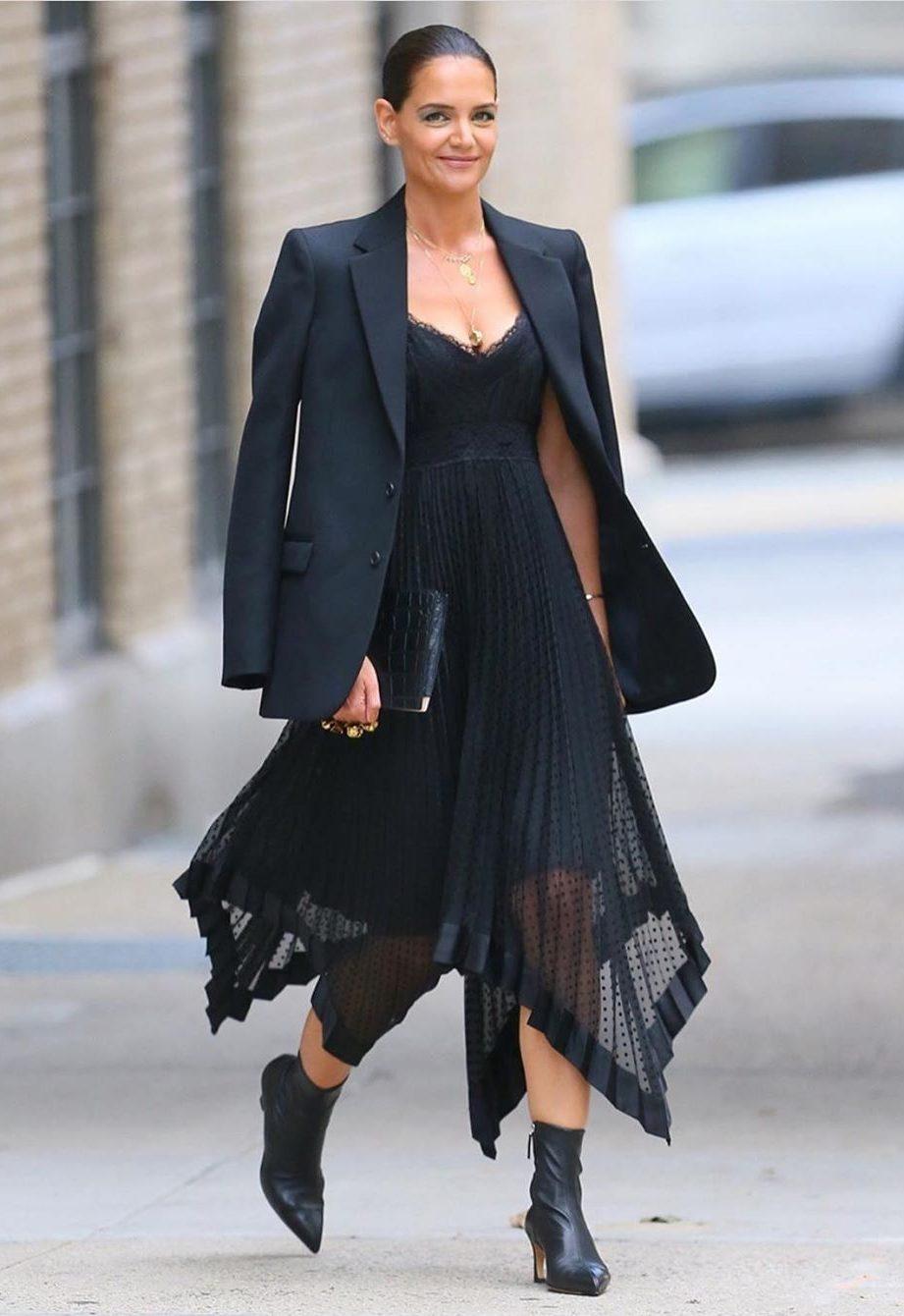 Девушка в черном асимметричном платье и жакет и ботильоны