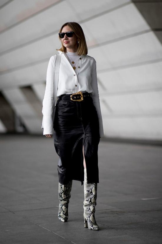 Девушка в черной кожаной юбке, белая рубашка и сапоги трубы из змеиной кожи