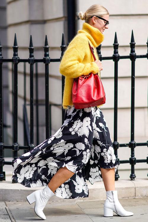 Девушка в черной юбке с цветочный принтом, желтый свитер и белые ботильоны