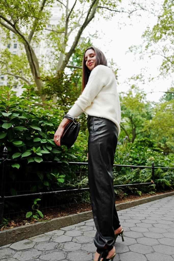 Девушка в черных брюках, белый свитер и сумка
