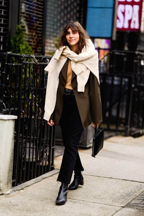 Девушка в черных брюках, блейзер оверсайз и бежевый свитер на шее