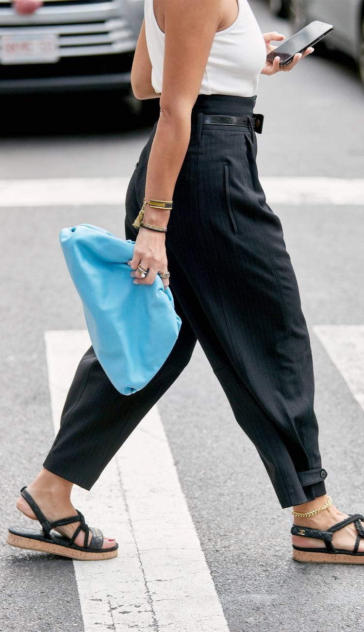 Девушка в черных брюках с завышенной талией, белая майка и черные сандалии