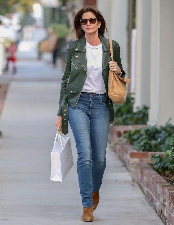 Девушка в джинсах, белая футболка и зеленая кожаная куртка