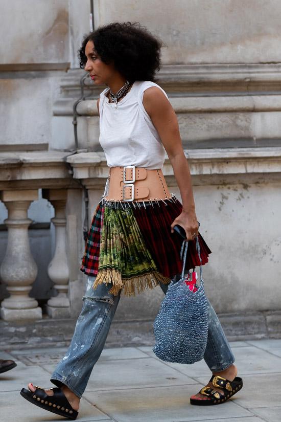 Девушка в джинсах, белая майка, плиссированная юбка с толстым ремнем и черные сандалии