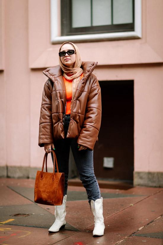 Девушка в джинсах, белые ковбойские сапоги, коричневый пуховик и бежевый шарф
