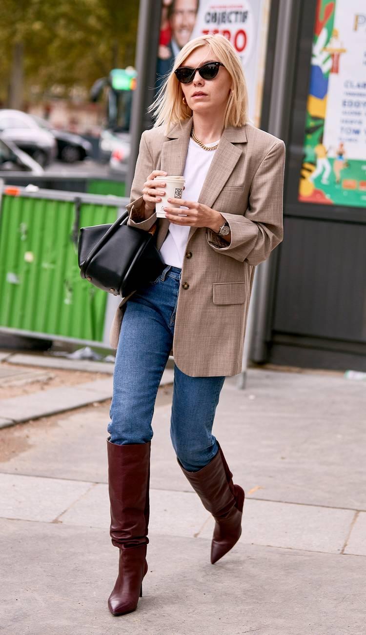 Девушка в джинсах, коричневые высокие сапоги и коричневый жакет