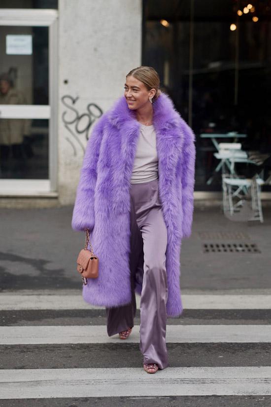 Девушка в фиолетовой шубе, атласные брюки и белая футболка