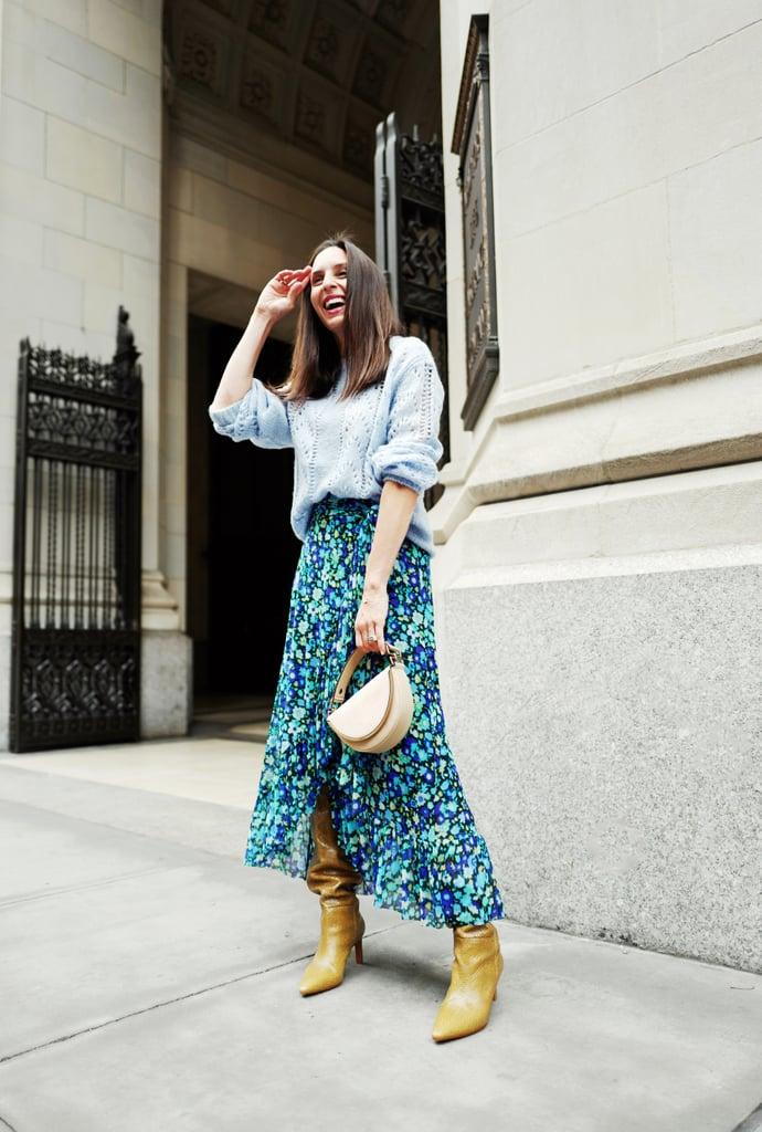 Девушка в голубой юбке миди с цветами, вязаный свитер и коричневые сапоги гармошка