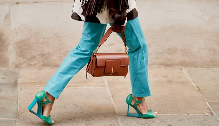 Девушка в голубых брюках, босоножки на каблуке и коричневая сумочка