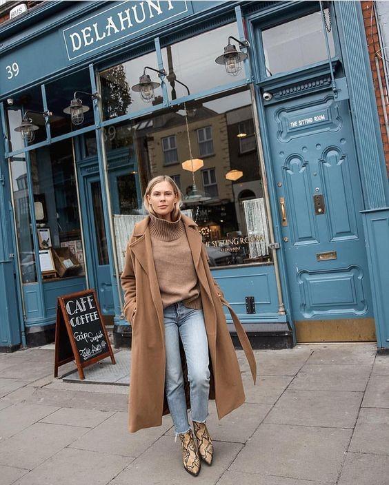 Девушка в голубых джинсах, бежевый свитер и классическое пальто и змеинные ботильоны