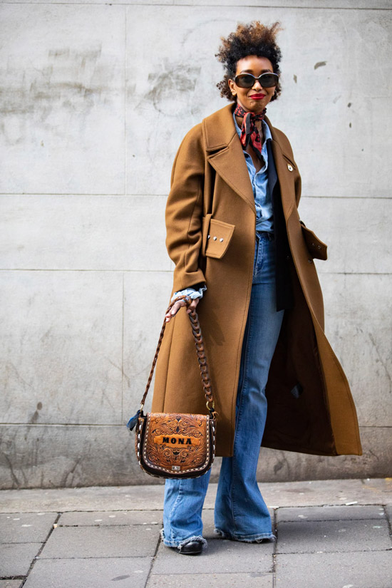 Девушка в голубых джинсах клеш, коричневое пальто и сумочка