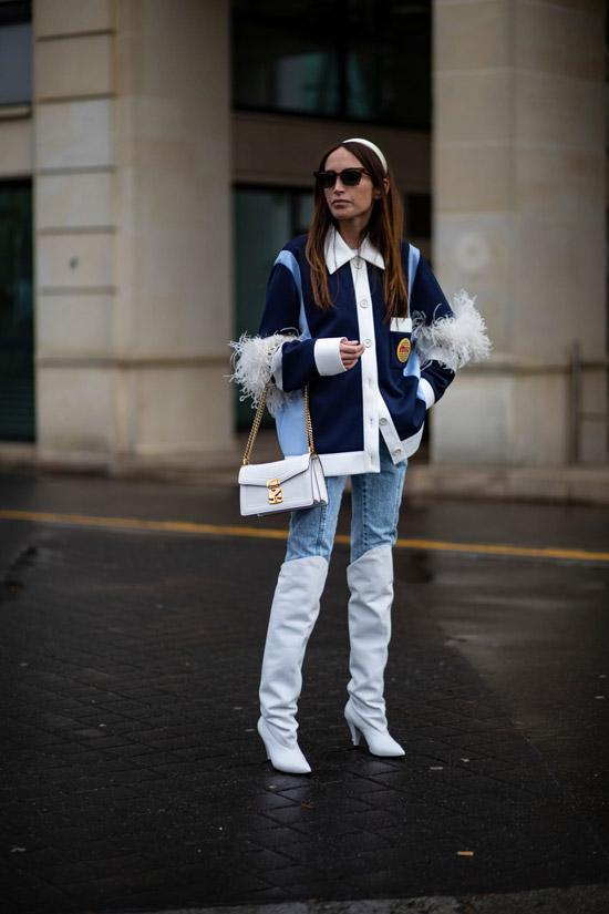Девушка в голубых джинсах, высокие белые сапоги и джинсовая куртка