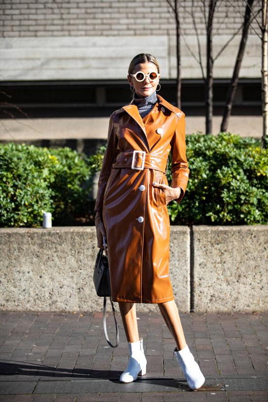Девушка в коричневом кожаном плаще с поясом и белые ботильоны на низом каблуке