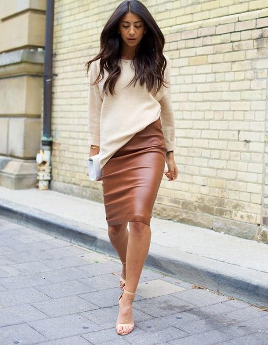 Девушка в коричневой кожаной юбке, бежевый свитшот и босоножки