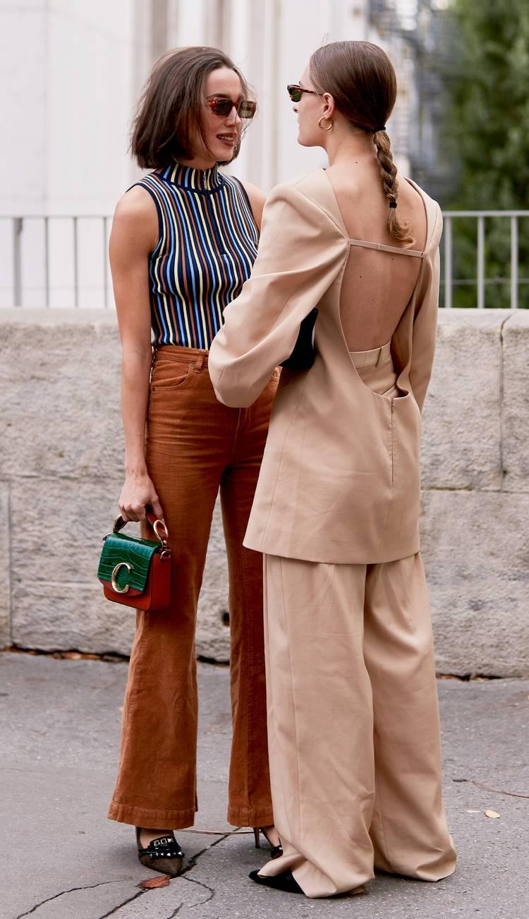 Девушка в коричневых брюках клеш, полосатый топ и маленькая сумочка