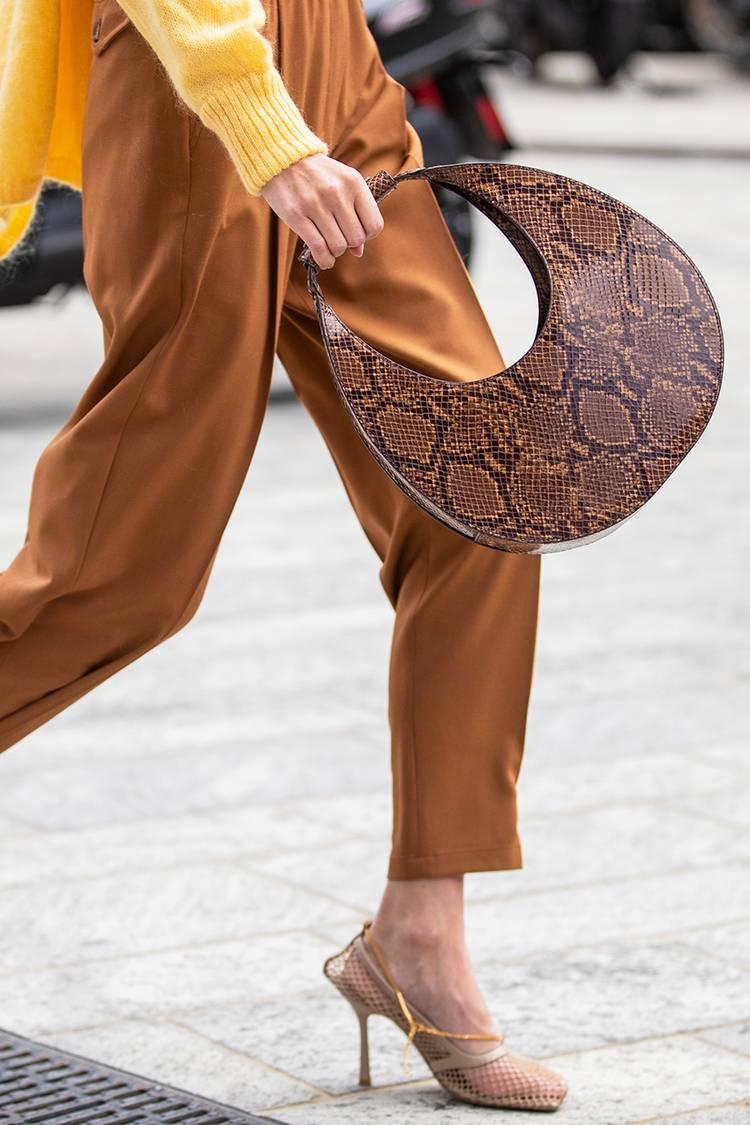 Девушка в кориневых брюках, бежевые босоножки и круглая сумка со змеиным принтом