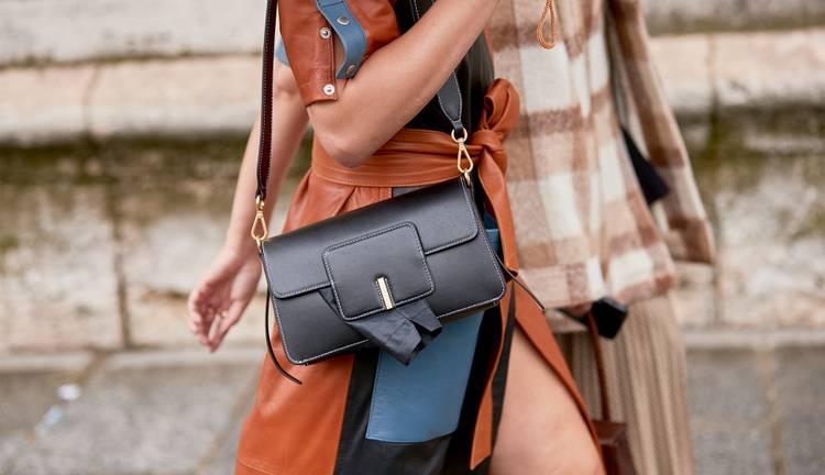 Девушка в кожаной юбке, черная сумочка