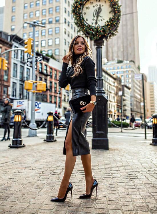 Девушка в кожаной юбке с разрезом, черная водолазка и туфли на шпильке