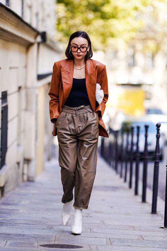 Девушка в кожаных брюках, черный топ, коричневый кожаный жакет и белые ботильоны